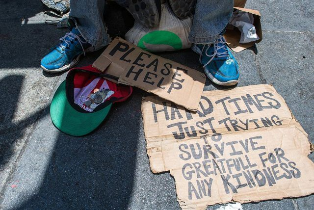 Signs and money laid out on a sidewalk.