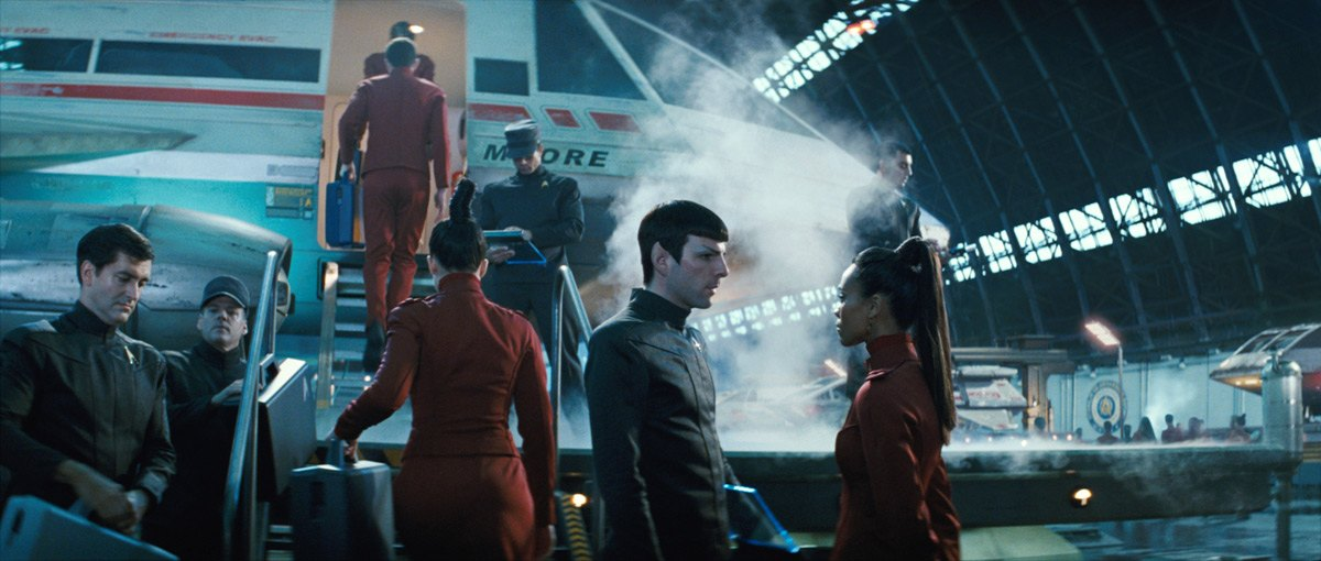 Spock and Uhura have a conversation in front of a plane in a hangar