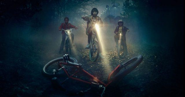 Promotional art from Netflix's 'Stranger Things' shows Lucas, Mike and Dustin on their bikes in front of Will's abandoned bike.