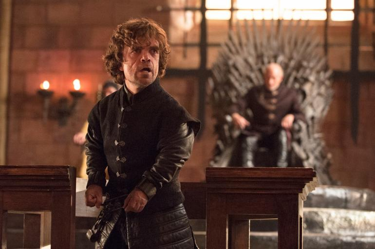 Tyrion Lannister on Game of Thrones Season 4 with a man in the background on a throne