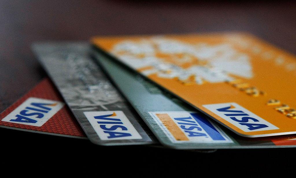 Visa credit cards are arranged on a desk