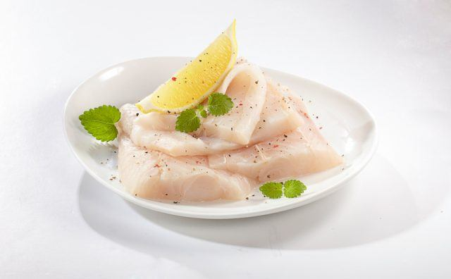 white fish in a white plate with lemon slice