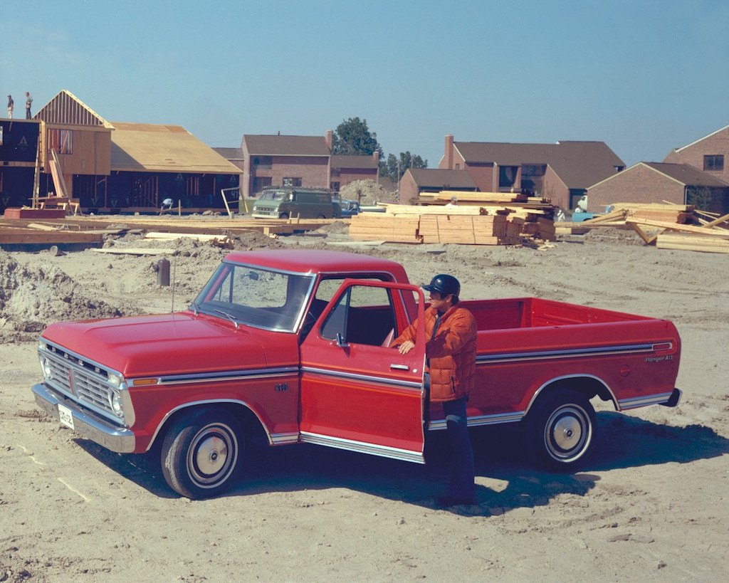 A red 1975 Ford F-150 sits parked in front of a construction site