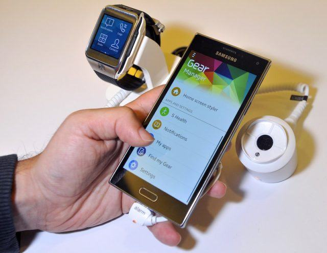 A Samsung employee demonstrates the new Samsung Z910F Smartphone (R) and the SM-R380 Smartwatch (L) at the Tizen Developer Conference in San Francisco, California on June 3, 2014. AFP PHOTO/JOSH EDELSON