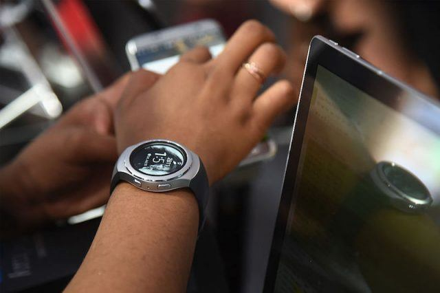 SPRINGFIELD, NJ - JULY 30: A brand ambassador wears a Samsung Gear S2 smart watch while showing a consumer the Samsung Galaxy S7 smart phone inside The Samsung Experience at the PGA Championship 2016 at Baltusrol Golf Club on July 30, 2016 in Springfield, New Jersey.