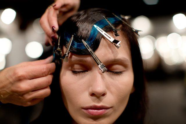 A hairdresser places on a model a blue dyed natural extension at the Mercedes Benz Fashion Week