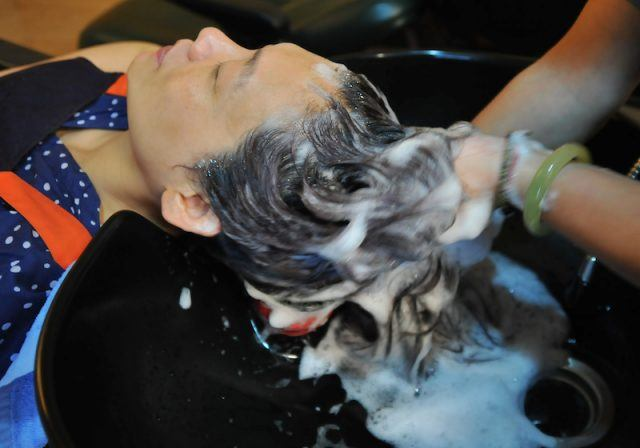 This photograph taken on July 29, 2013 shows a hairdresser washing the hair of a client at a salon in Taipei.
