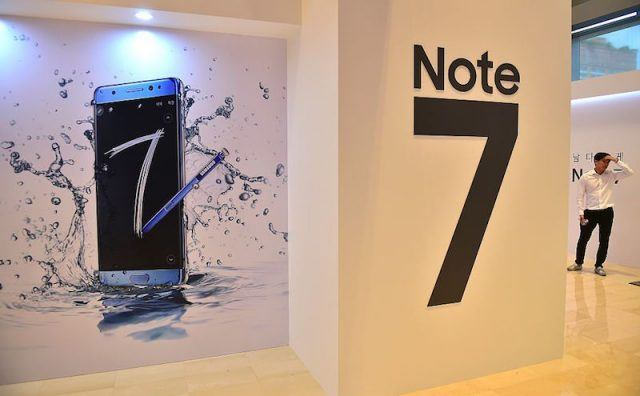 A man stands by signboards of Samsung Galaxy Note7 during a showcase to mark its domestic launch in Seoul on August 11, 2016. The Note7 will be available starting August 19, with a price of 988,900 won (897 USD) in South Korea. / AFP / JUNG YEON-JE