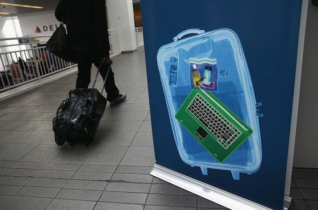 A traveler walks past a newly-opened TSA Pre-check application center at Terminal C of the LaGuardia Airport on January 27, 2014 in New York City. Once approved, travelers can use special expidited Precheck security lanes. They can also leave on their shoes, light outerwear and belt, as well as keep their laptop and small containers of liquids inside carry-on luggage during security screening. The TSA plans to open more than 300 application centers across the country.
