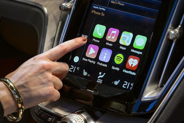 A visitor presses the new Apple's CarPlay touch-screen commands inside the Volvo Estate concept car displayed at the Swedish carmaker during the press day of the Geneva Motor Show in Geneva, on March 4, 2014. Apple announced that autos will roll out this year with CarPlay technology making iPhones helpful road-trip companions, complete with Siri tending to messages. Ferrari, Volvo, and Mercedes-Benz will show off the technology this week at a car show in Geneva, but the long list of auto makers incorporating it into models included Honda, BMW, Toyota, and General Motors. AFP PHOTO / FABRICE COFFRINI