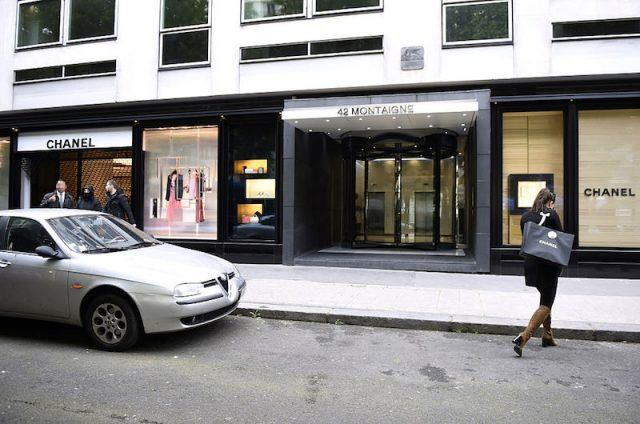 A woman carrying a Chanel shopping bag walks past the Chanel shop on Rue de Montaigne in Paris