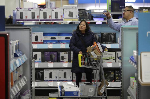 A woman receives help from a worker as she shops for electronics and other items at a Best Buy