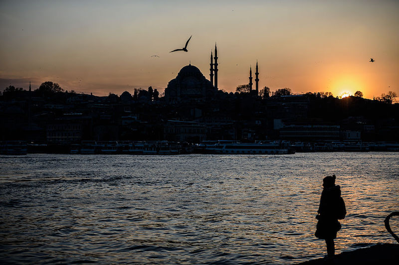 A woman stands on the shore of the Bosphorus river's Golden Horn at Karakoy district as the Suleymaniye Mosque silhouettes against the evening sky, in Istanbul on January 25, 2016. / AFP / OZAN KOSE