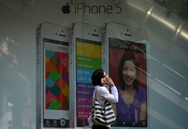 A woman uses a mobile phone as she walks past an Apple iPhone 5 poster outside a store in Beijing on September 11, 2013. Apple's lower-cost iPhone 5C will retail for more than 700 USD in China, putting it out of reach of most consumers and raising questions over the firm's ability to build sales in the world's biggest mobile market. AFP PHOTO / WANG ZHAO