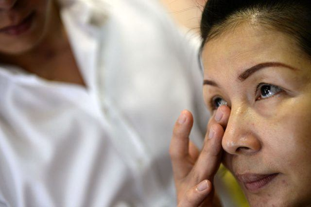 Amy Ong, 50-year-old visitor receives a facial anti-ageing treatment at the Beauty Asia trade show in Singapore on February 18, 2014. The three-day Beauty Asia trade show exhibits the latest products and trends in the beauty, spa and health industry. AFP PHOTO/ROSLAN RAHMAN