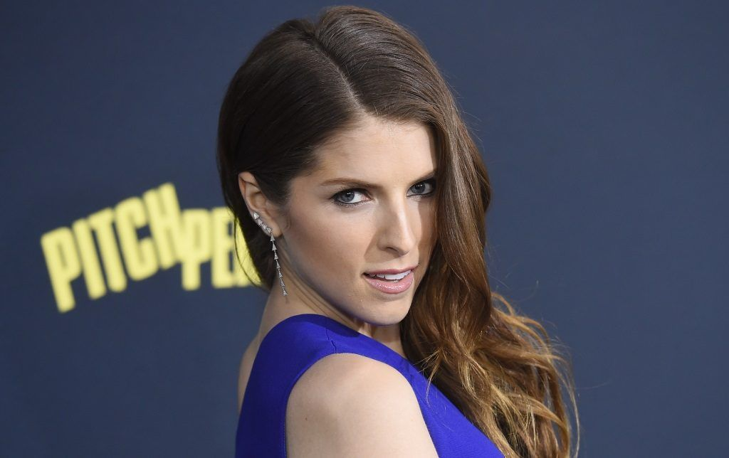 Actress Anna Kendrick looks over her shoulder while posing on the red carpet.