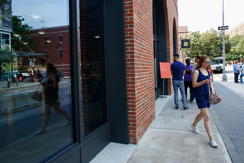 A woman walks by the new Brooklyn Apple