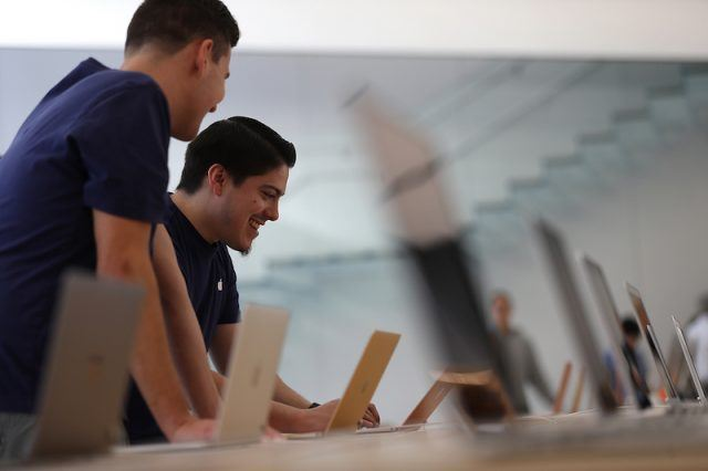 """Apple Store employees look at a display of MacBook laptops during a press preview of the new flagship Apple Store on May 19, 2016 in San Francisco, California. Apple is preparing to open its newest flagship store in San Francisco's Union Square on Saturday May 21. The new store features new design elements as well as community programs including the """"genius grove"""" where where customers can get support under a canopy of local trees and """"the plaza"""" a public space that will be open 24 hour a day. Visitors will enter the store through 42-foot tall sliding glass doors."""