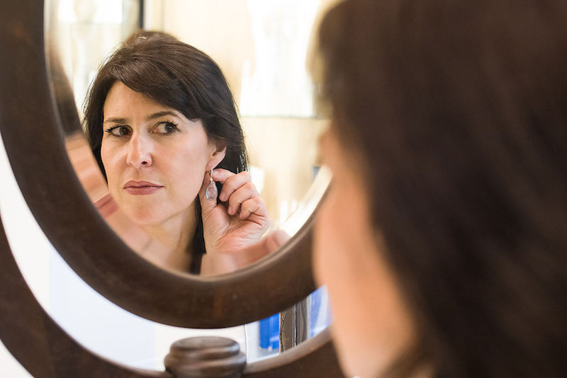 A jeweler inspects her earring in a mirror