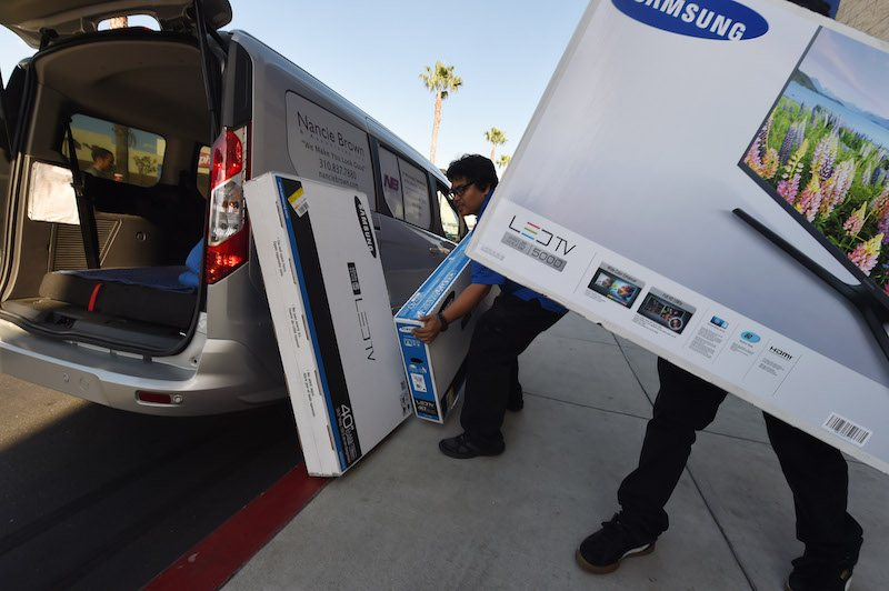 """Best Buy staff load a television during a Black Friday sale in Los Angeles, California on November 27, 2015. The US holiday shopping season kicks off with """"Black Friday"""" -- the day after the Thanksgiving holiday -- with a frenzy expected at stores around the country as retailers slash prices. AFP PHOTO/ MARK RALSTON / AFP / MARK RALSTON"""