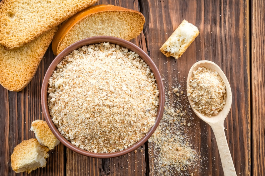 Breadcrumbs in a bowl with bread slices