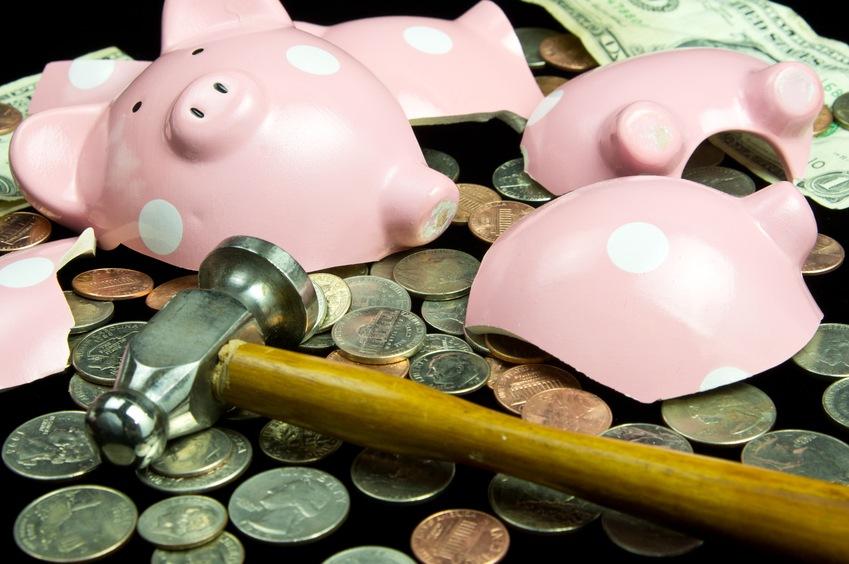Broken piggy bank with coins & hammer, going broke