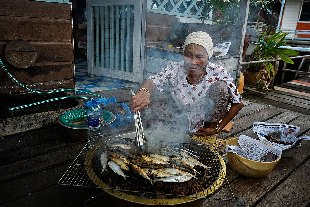 A muslim woman cooks fresh fish in Brunei