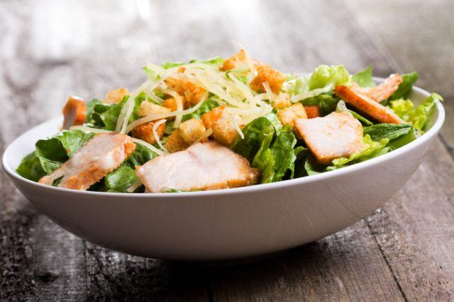 Caesar salad with chicken on a white bowl.