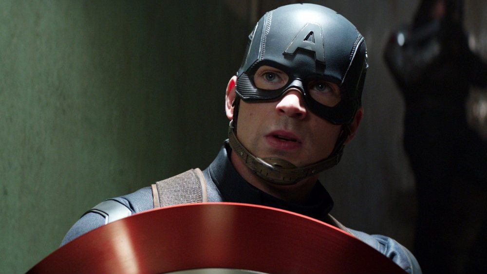 Chris Evans holds up a shield and wears his Captain America suit in Captain America Civil War
