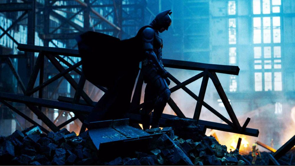 Batman is standing on a head of rubble in The Dark Knight.
