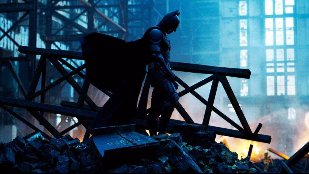 Batman is standing on a head of rubble in The Dark Knight.