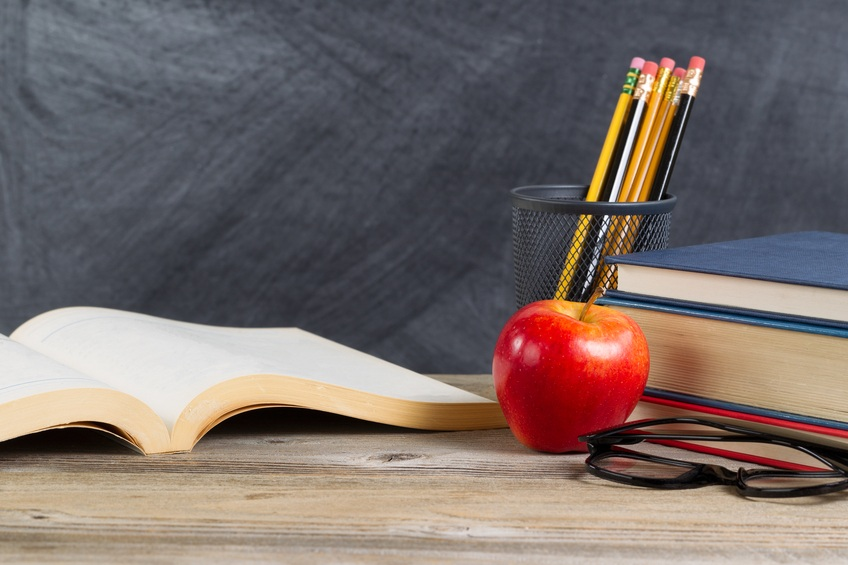 Desktop with books, red apple, reading glasses, and pencils