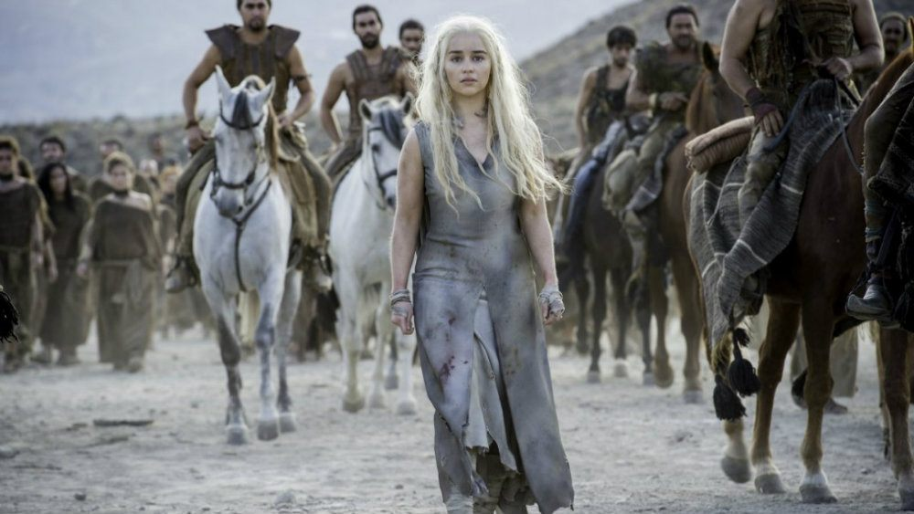 Emilia Clarke walks as men mounted on horses gather behind her in Game of Thrones