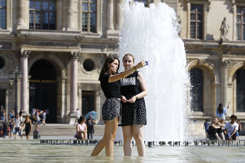 People take a selfie while wading in a fountain at the Louvre Museum
