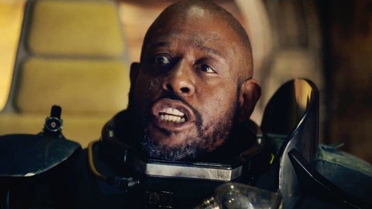 Saw Gerrera, wearing a black armored suit, and bearing his teeth