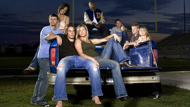 Characters from 'Friday Night Lights' sitting at the bank of a car on a football field.
