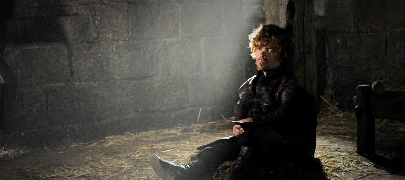 Tyrion sits up against a pillar in chains, looking down on the crowd while deeply contemplating