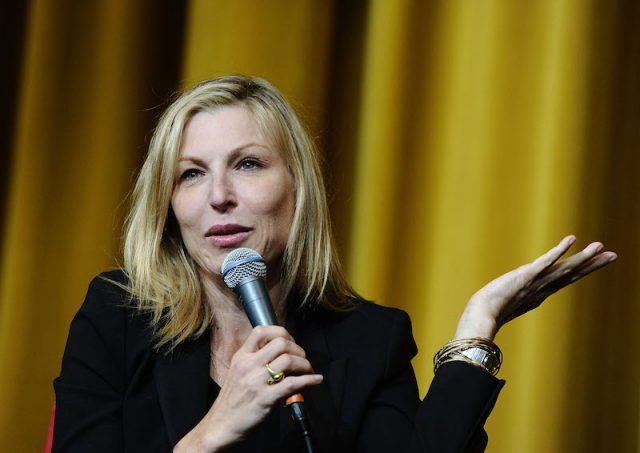 Tatum O'Neal holds a microphone while speaking onstage.