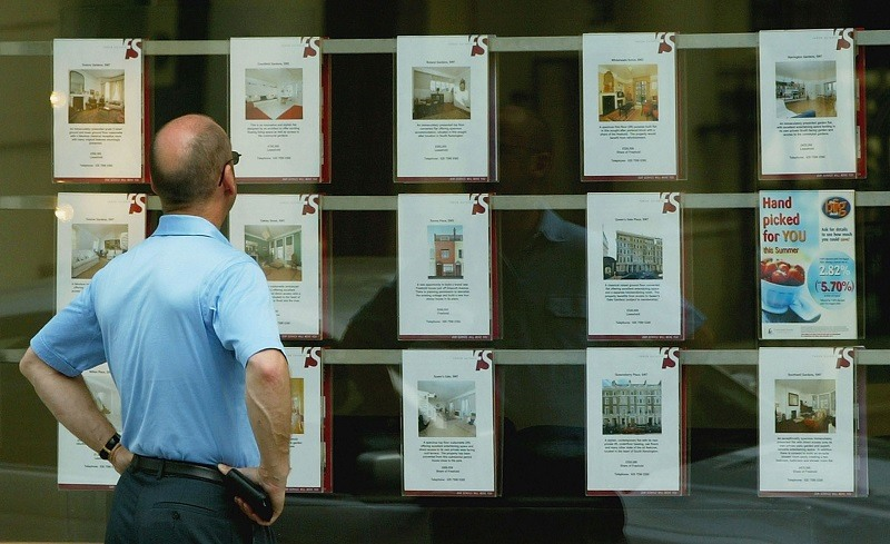 A man, considering buying a house, checks out local real estate