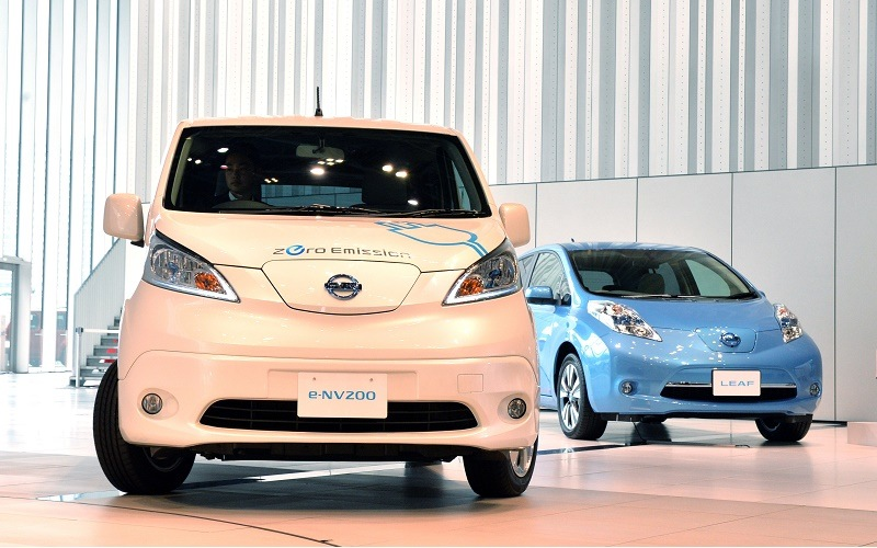 """This picture taken on June 9, 2014 shows Japanese auto maker Nissan Motor's electric vehicles """"e-NV200"""" (L) and """"Leaf"""" (R) at the company's headquarters in Yokohama, suburban Tokyo. Global automakers are locked in a showdown evoking the video format wars of the 1980s, as they bet on what eco-friendly vehicles will prevail in the battle for dominance of the burgeoning low-emissions sector."""