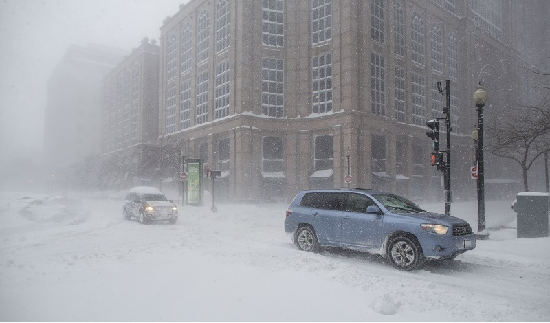 Cars drive down Surface Rd. during winter storm Neptune which dropped over a foot of snow February 15, 2015 in Boston, Massachusetts. This is the fourth major storm to hit the New England region that has already seen more than 6 feet of snow in some areas.