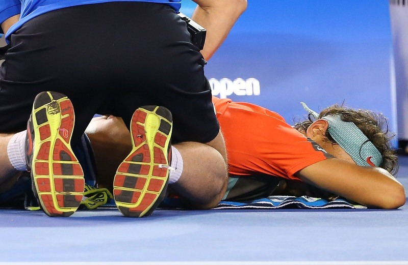 A tennis player receives a back massage to help with muscle recovery