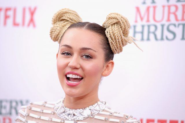 Miley Cyrus smiling and wearing a diamond-studded gown at a movie premiere.