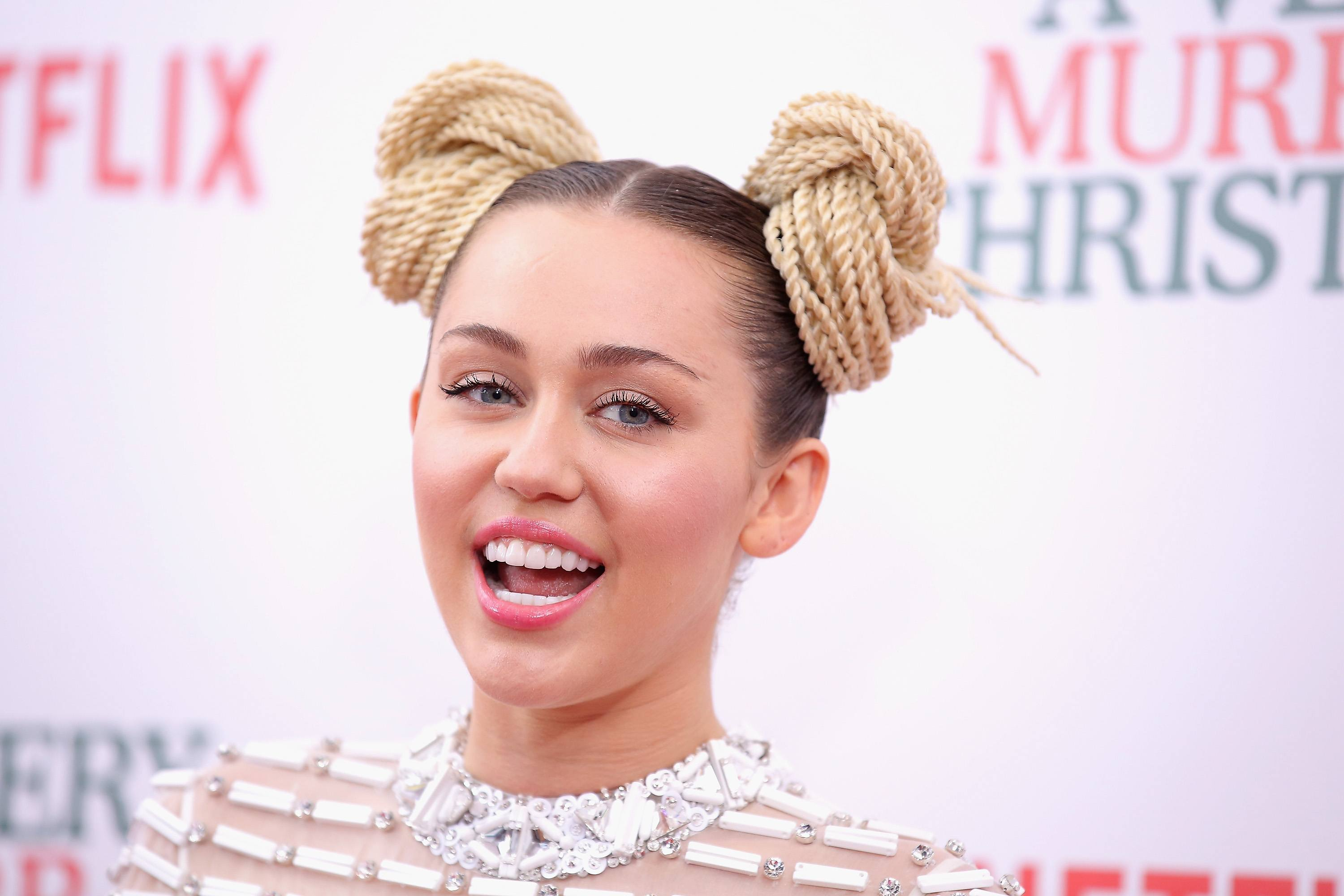 Miley Cyrus is smiling on the red carpet with two twisted hair buns.