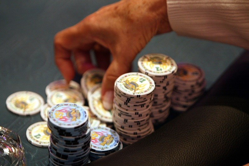 A poker player prepares to throw her chips on the table