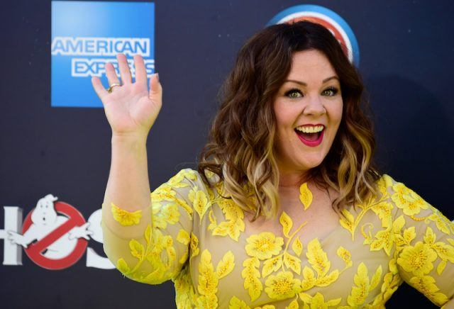 Melissa McCarthy smiling and waving on a red carpet.
