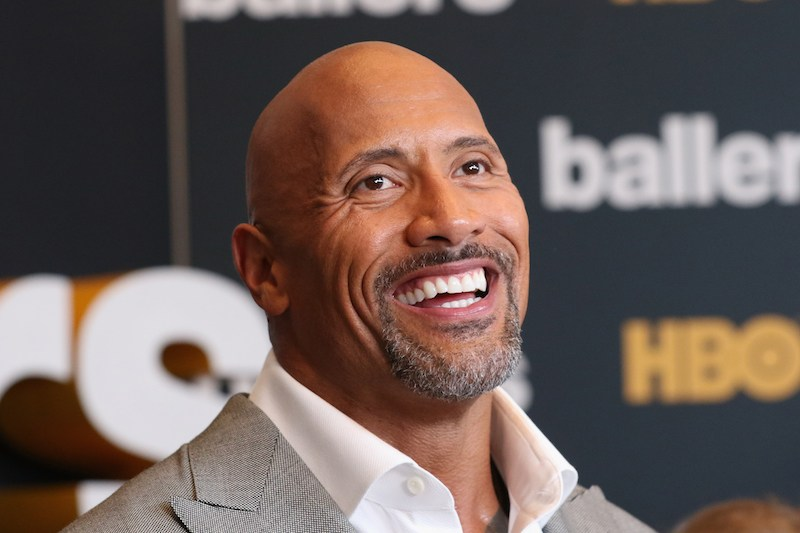 Dwayne Johnson is smiling in a grey suit jacket on the red carpet.