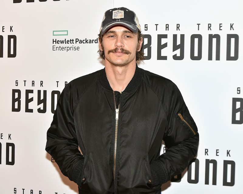 James Franco smiles while taking photos in a black jacket and cap.