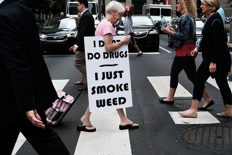 A female cannabis consumer walks with a sign supporting legalizing marijuana