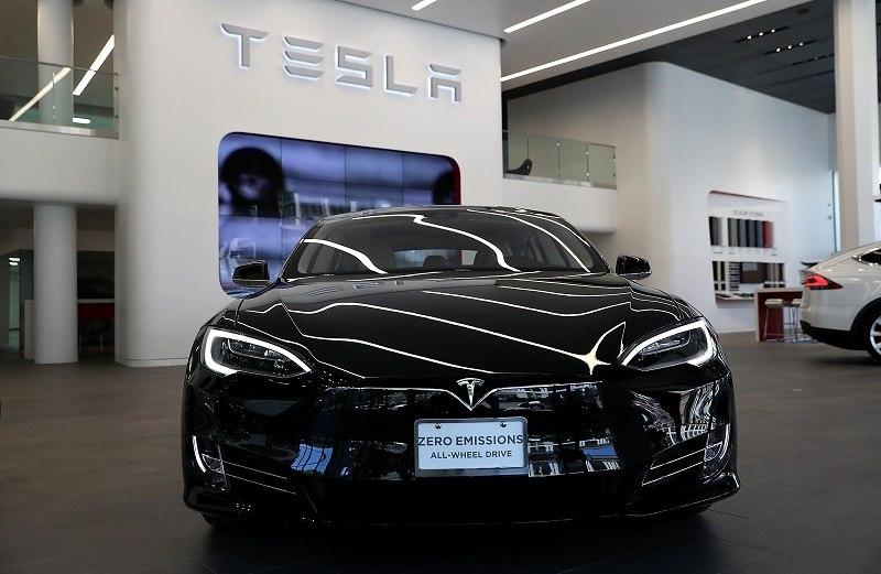 Tesla Model S in front of a Tesla logo.